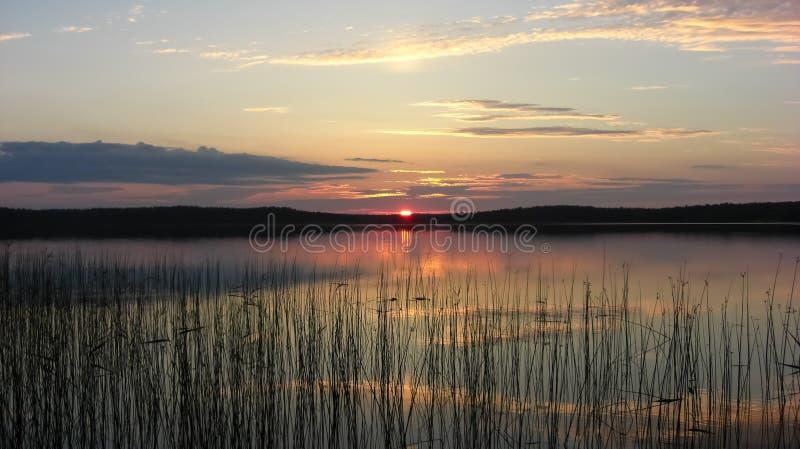 Coucher du soleil de la Carélie sur le lac dans les bois images libres de droits