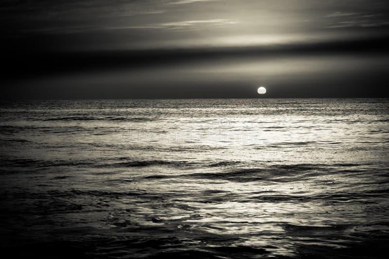Coucher du soleil de lever de soleil au-dessus des ressacs de mer en noir et blanc images stock