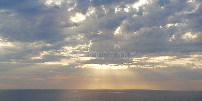 Coucher du soleil de mer Les rayons du coucher de soleil percent les nuages Paysage marin Fond photos libres de droits
