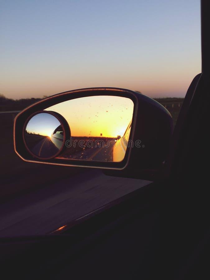 Coucher du soleil de miroir de voiture sur une commande quotidienne image libre de droits