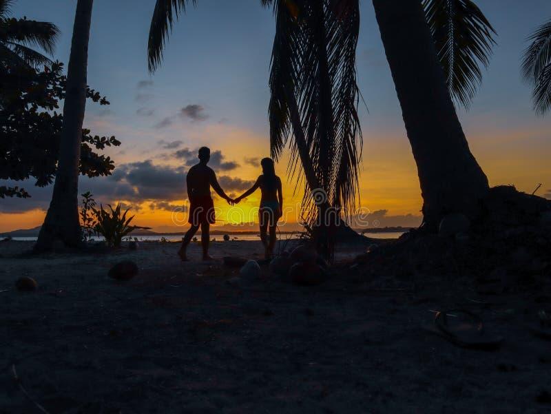 Coucher du soleil de observation de couples avec des palmiers en île de Candaraman dans Balabac Philippines photographie stock libre de droits