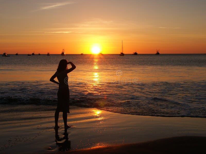 Coucher du soleil de observation de jeune femme photo stock