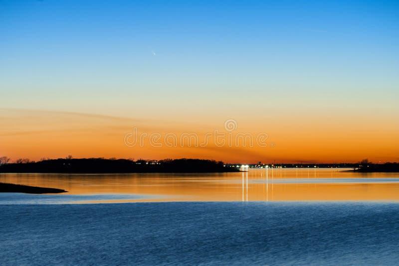 Coucher du soleil de Panstarrs de comète à travers un lac photographie stock libre de droits