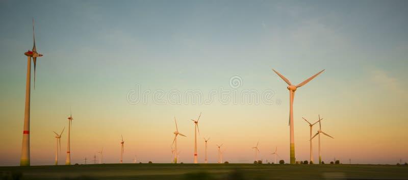Coucher du soleil de paysage avec des moulins à vent Source de renouvellement d'électricité photos stock