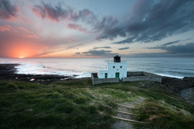Coucher du soleil de phare de Bamburgh photo libre de droits