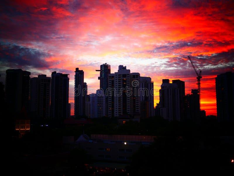 Coucher du soleil derrière des bâtiments avec le beau ciel nuageux image libre de droits