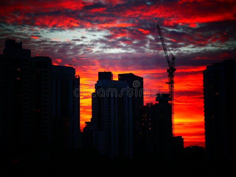 Coucher du soleil derrière des bâtiments avec le beau ciel nuageux photographie stock