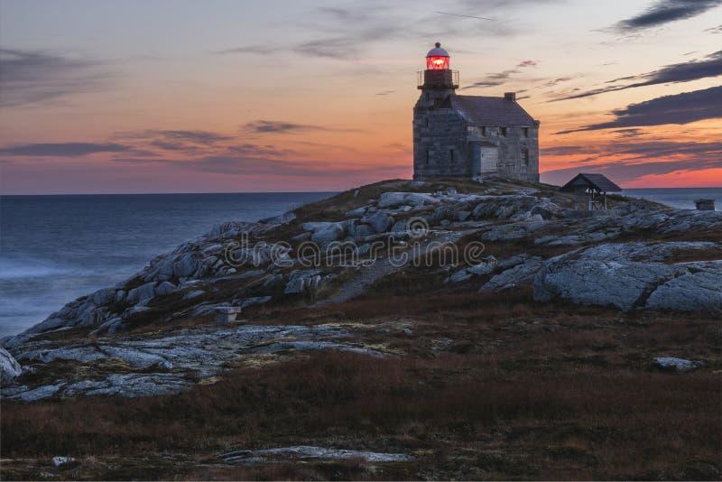 Coucher du soleil derrière le phare rose de blanche photos libres de droits