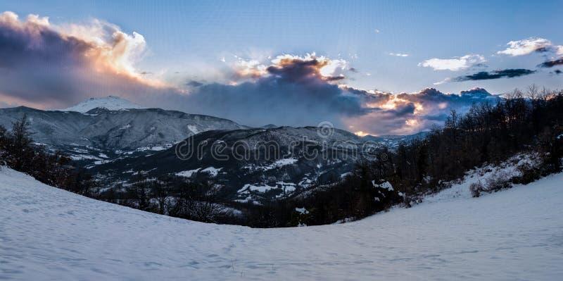 Coucher du soleil derrière les montagnes congelées, avec la neige et les nuages image libre de droits