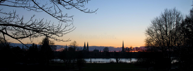 Coucher du soleil derrière les tours d'église de Luebeck, Allemagne du nord photo libre de droits