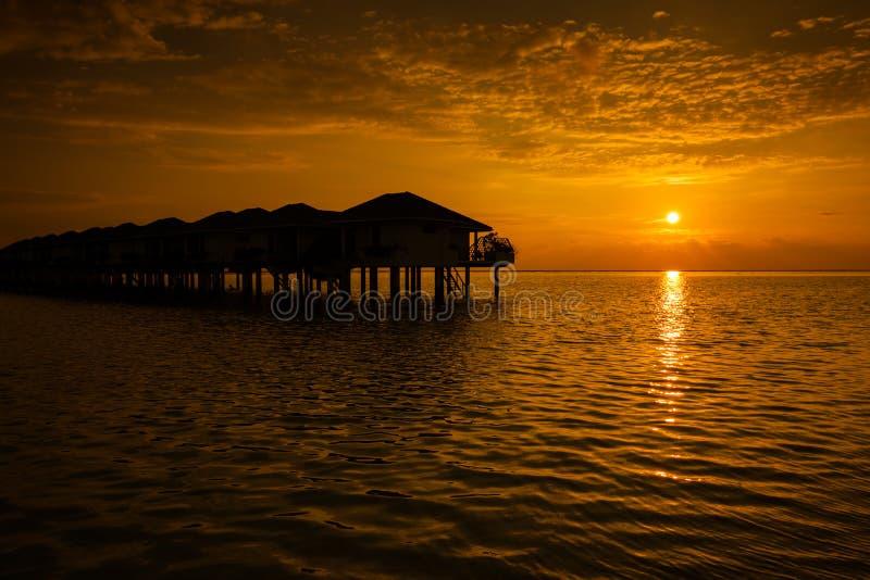 Coucher du soleil des Maldives avec la silhouette de villas de l'eau image libre de droits