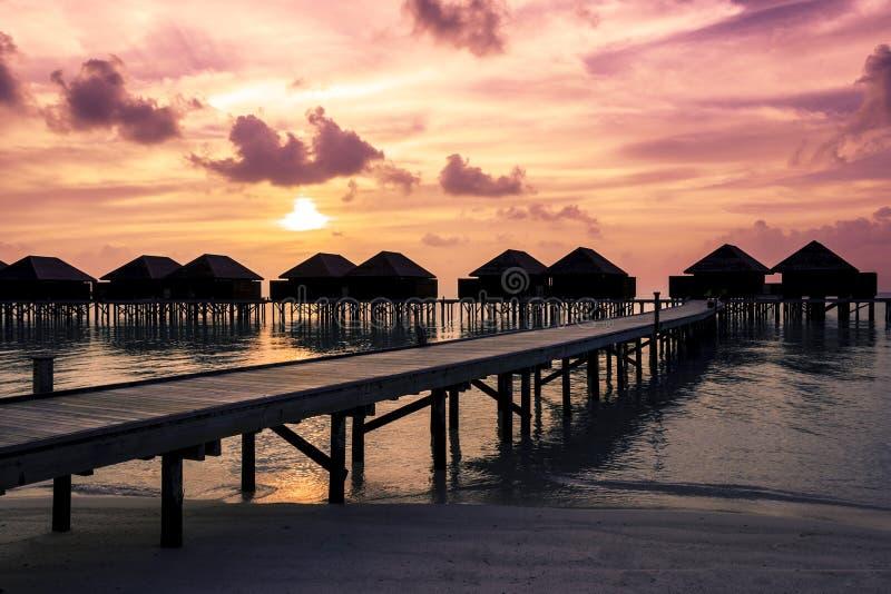 Coucher du soleil des Maldives avec la silhouette de villas de l'eau photos libres de droits