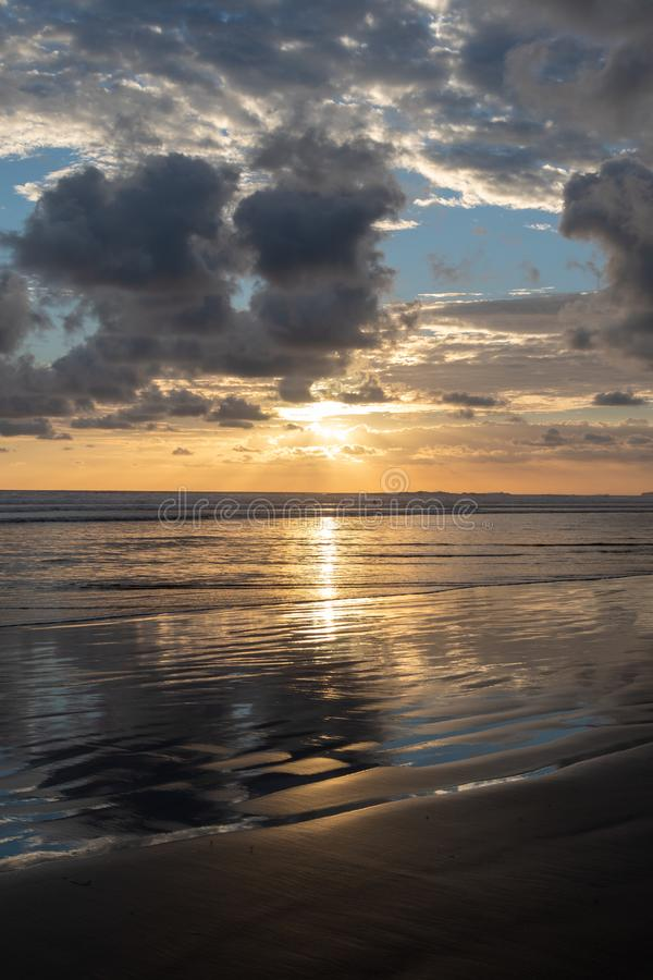 Coucher du soleil dramatique avec Relections sur une plage sablonneuse images libres de droits