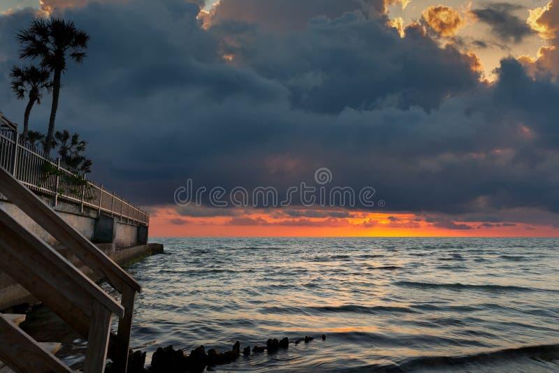 Coucher du soleil dramatique d'océan avec le mur et les palmiers de mer dans le premier plan image libre de droits