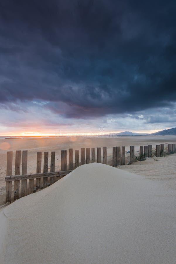 Coucher du soleil dramatique et nuages de tempête au-dessus de plage à Tarifa, Espagne photo stock