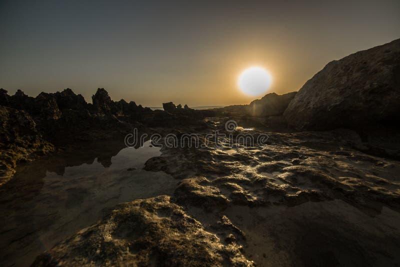 Coucher du soleil durci de coucher du soleil de magma de lave au-dessus de la mer et des montagnes reflété dans les montagnes et  photographie stock