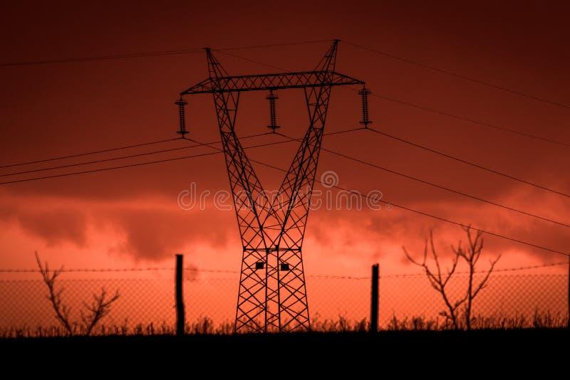 Coucher du soleil effrayant, avec le ciel et les nuages rouges, après tempête Actionnez les pylônes et les barrières industrielle photographie stock libre de droits