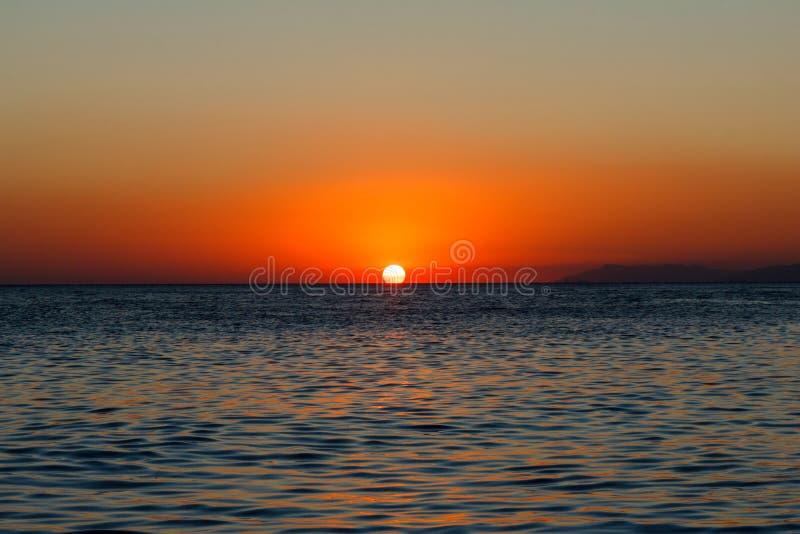 Coucher du soleil en bronze de mer avec brusquement et mer bleue photo libre de droits