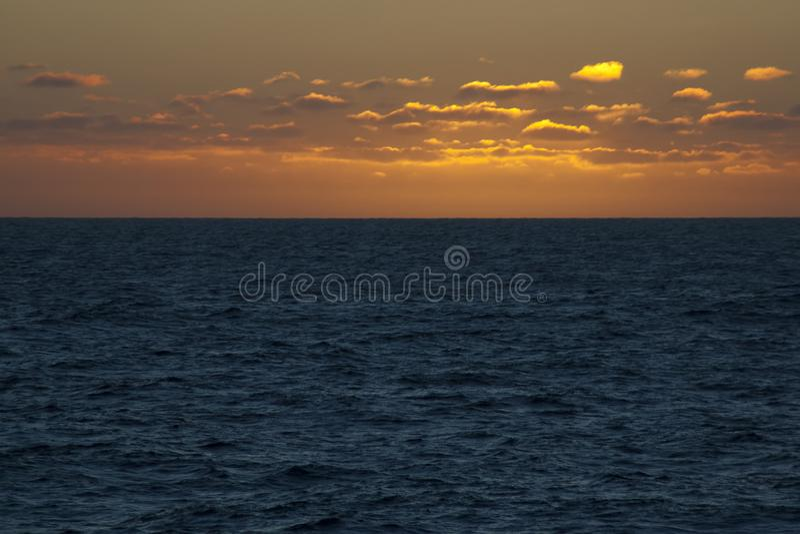 Coucher du soleil en mer, ciel orange photo stock