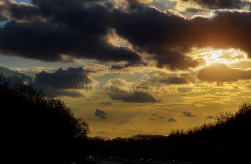 coucher du soleil en nuages avec des rayons de soleil au-dessus de route au horizont image libre de droits