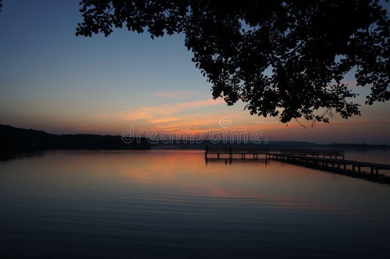 Coucher du soleil en retard par le lac au secteur polonais de Masuria (Mazury) photographie stock libre de droits