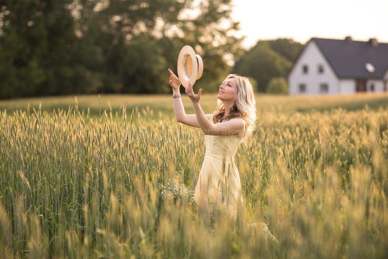 Coucher du soleil en ?t? Dur?e rurale Une jeune femme dans le domaine jette un chapeau Type rustique image stock