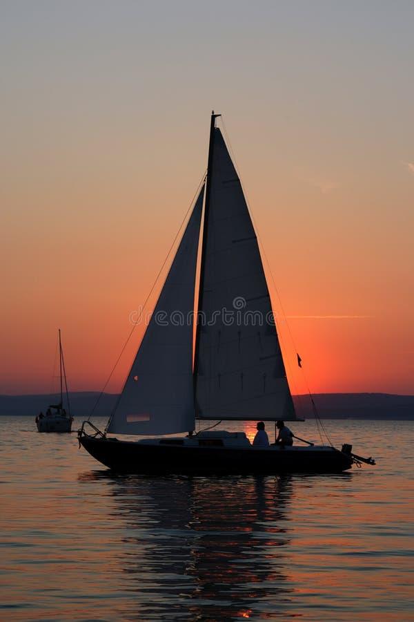Coucher du soleil et bateau avec des gens image libre de droits