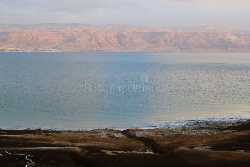 Coucher du soleil et crépuscule à la côte de la mer morte, des roches et de la plage salée avec la roche géologique et les couche image libre de droits