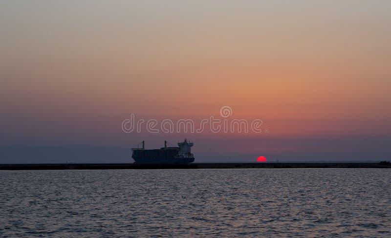 Coucher du soleil et le navire porte-conteneurs photographie stock