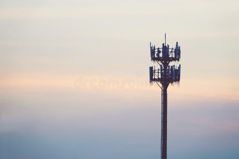 Coucher du soleil et mât grand avec l'antenne cellulaire photos libres de droits