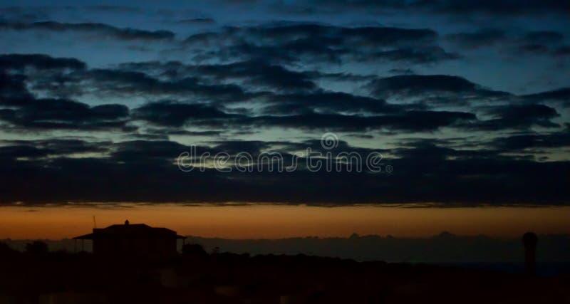 coucher du soleil et maison images stock