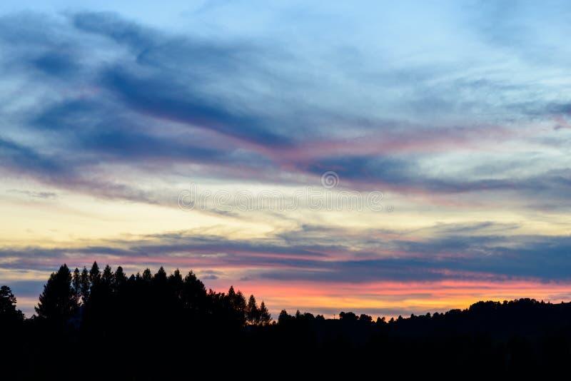 Coucher du soleil et nuages orageux au-dessus des champs et des collines image stock