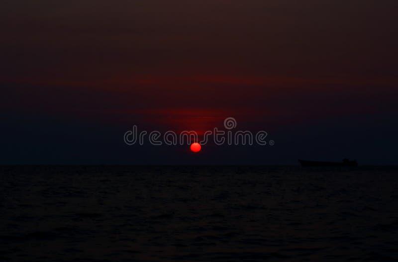 Coucher du soleil fonc? par la mer photo libre de droits
