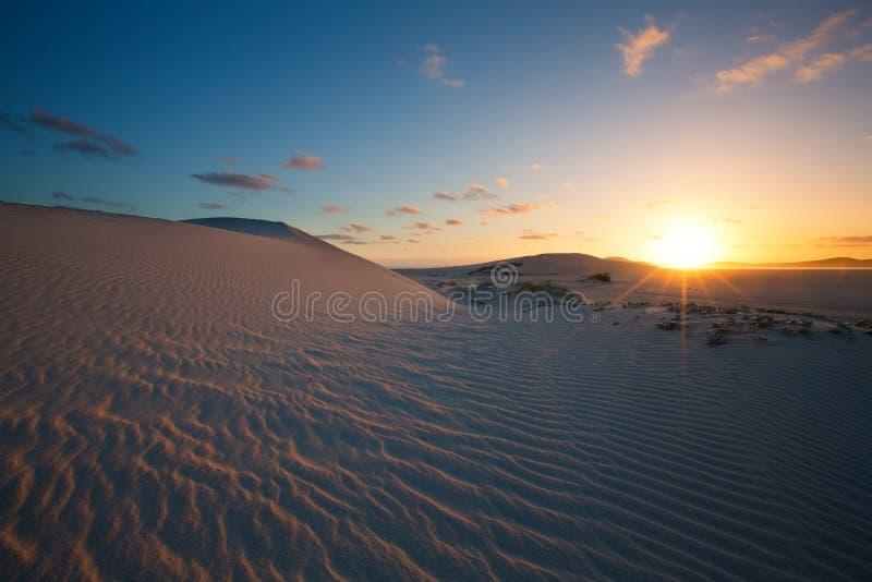 Coucher du soleil glorieux au-dessus de dune de sable ondulée à côté d'une lagune image stock