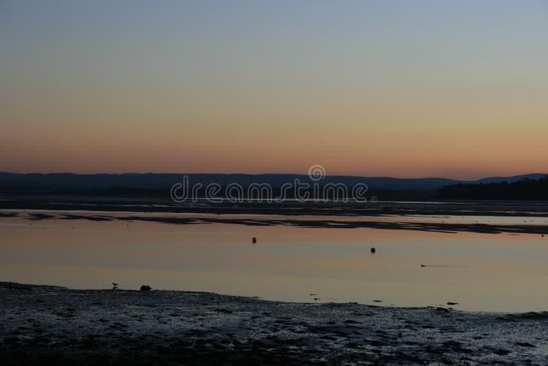 Coucher du soleil glorieux mais gelant au-dessus d'une baie côtière écossaise de village images libres de droits