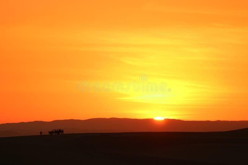 Coucher du soleil incroyable au-dessus des dunes de sable du désert de Huacachina avec la silhouette du buggy des sables de touri photographie stock