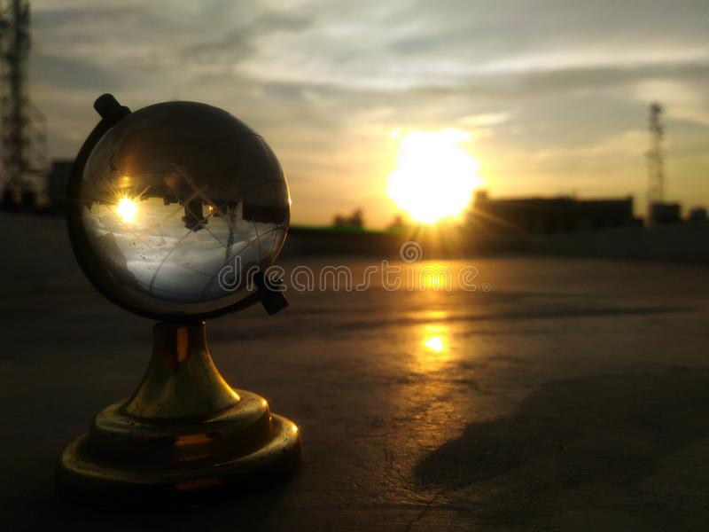 Coucher du soleil inverse par le globe photographie stock
