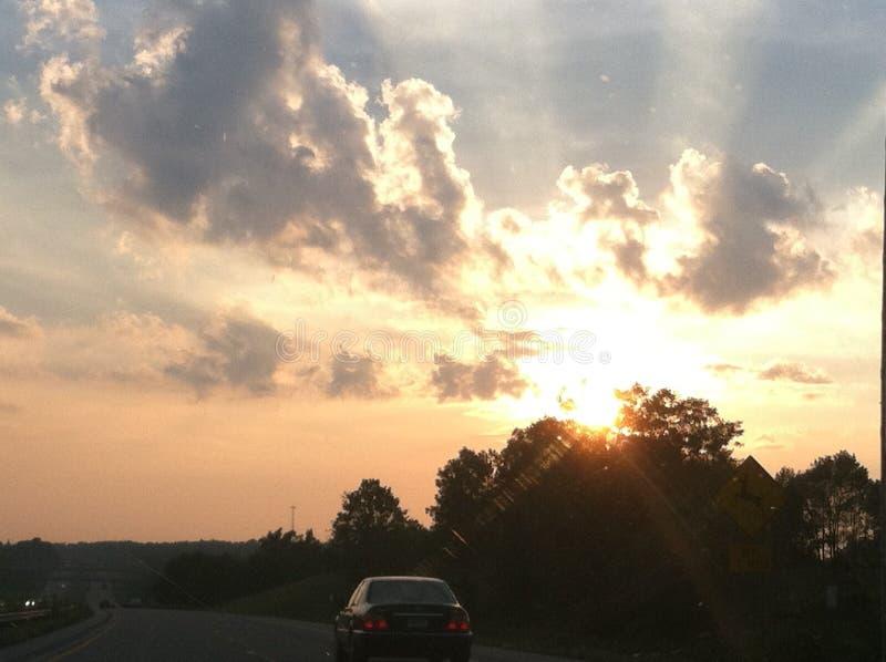 Coucher du soleil jetant un coup d'oeil au-dessus des arbres photo stock