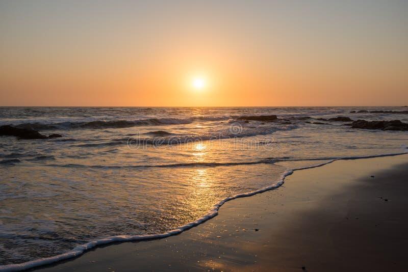 Coucher du soleil namibien coloré avec le bas soleil et de petites vagues image libre de droits