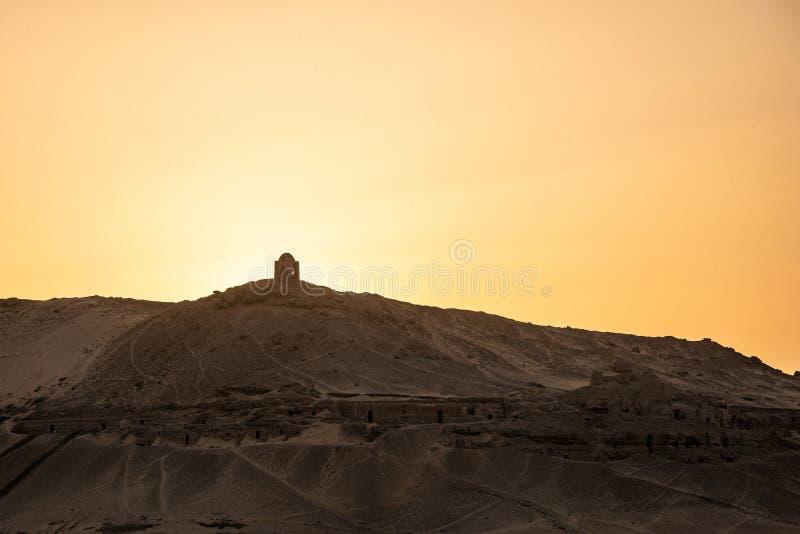 """Coucher du soleil Nile Aswan et Cisjordanie avec le vieil EL-Hawa de Qubbet de royaume de tombes - """"dôme des vents à la crête de  images libres de droits"""