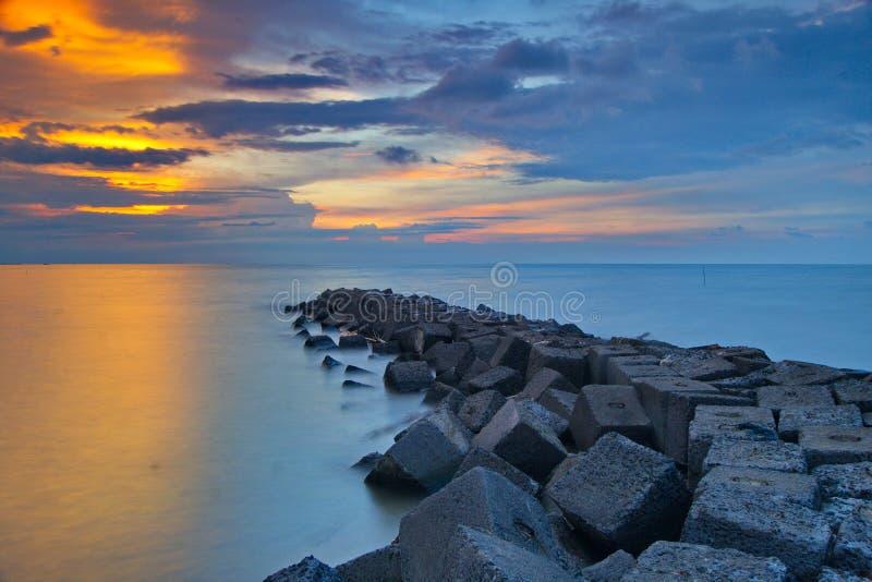 Coucher du soleil nuageux au-dessus des roches photographie stock libre de droits