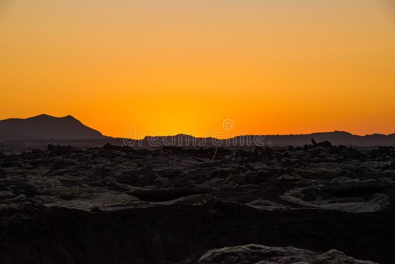 Coucher du soleil orange au-dessus de la terre en friche de lave photos libres de droits