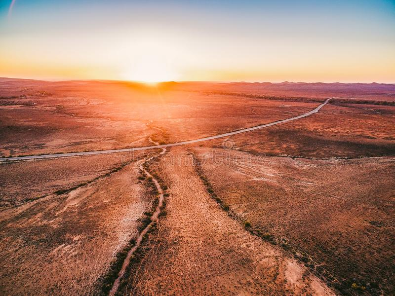 Coucher du soleil orange au-dessus de terre sèche et de route rurale photos stock