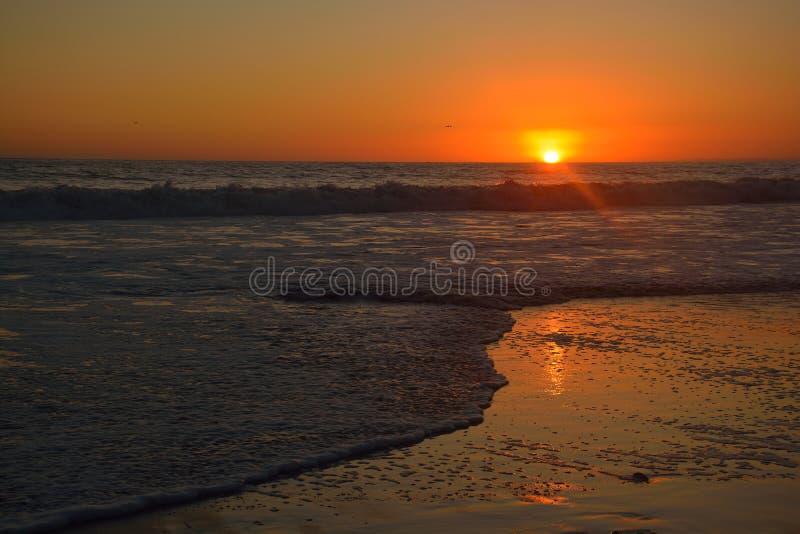 Coucher du soleil orange au-dessus des vagues à la plage de Santa Monica images stock