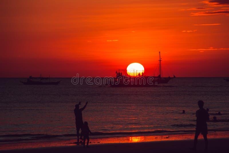 Coucher du soleil orange dramatique de mer avec des silhouettes de voilier et de personnes Jeunes adultes Voyage vers Philippines images stock