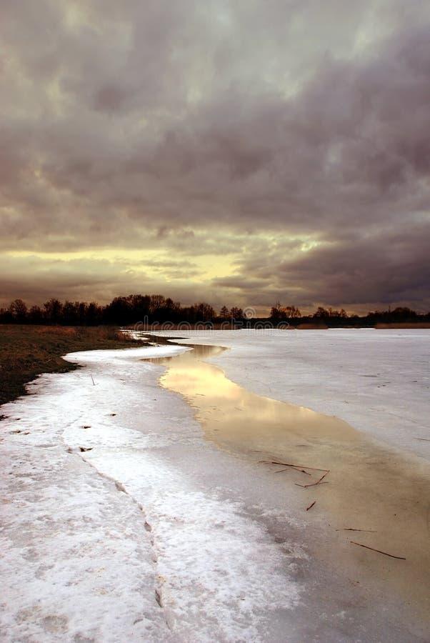 Coucher du soleil par un lac figé photographie stock
