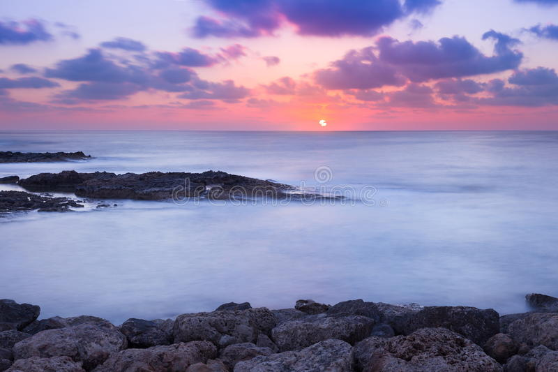 Coucher du soleil pourpre et rose au-dessus de rivage d'océan photos libres de droits
