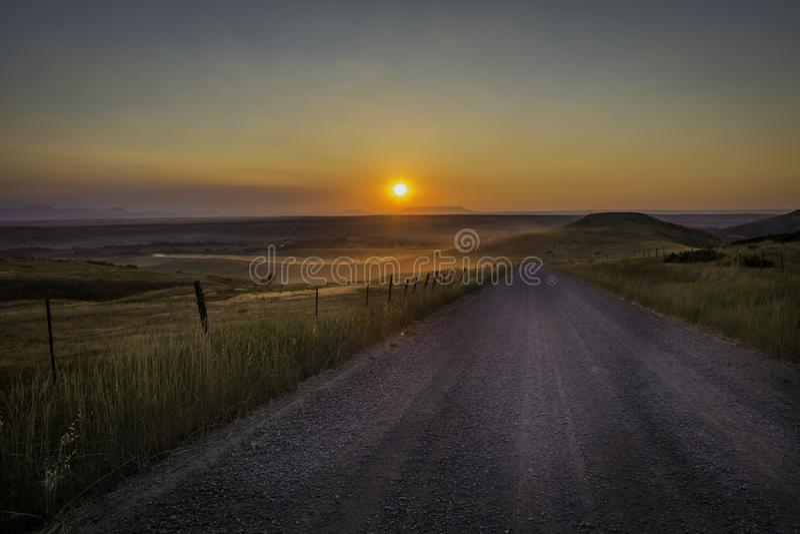 Coucher du soleil poussiéreux de chemin de terre en Amérique rurale photo stock