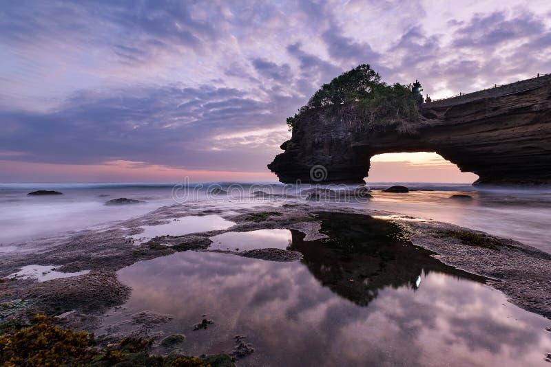 Coucher du soleil près de point de repère de touristes célèbre d'île de Bali - temple de sort et de Batu Bolong de Tanah photographie stock