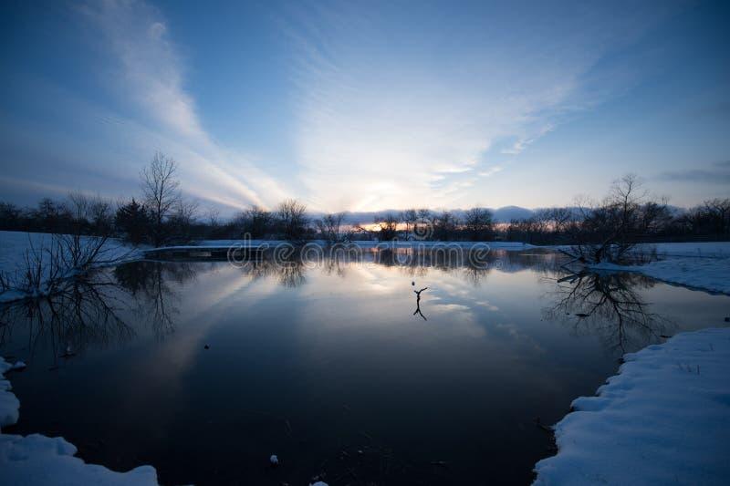 Coucher du soleil réfléchissant sur l'étang photographie stock libre de droits